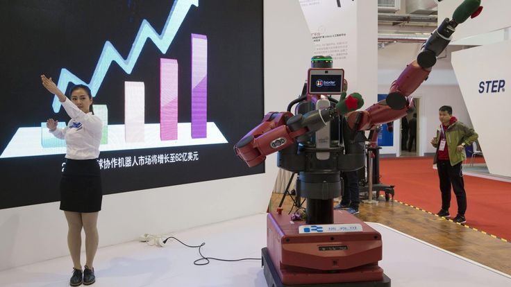 In this Friday, Oct. 21, 2016 photo, a Chinese woman demonstrates the ability of Baxter, an industrial robot from U.S. company Rethink Robotics, to follow her hand movements during the World Robot Conference in Beijing. China is showcasing its burgeoning robot industry as it seeks to promote use of more advanced technologies in Chinese factories and create high-end products that redefine the meaning of 'ÄúMade in China.'Äù China will have to make big strides to leap ahead of Germany, Japan…