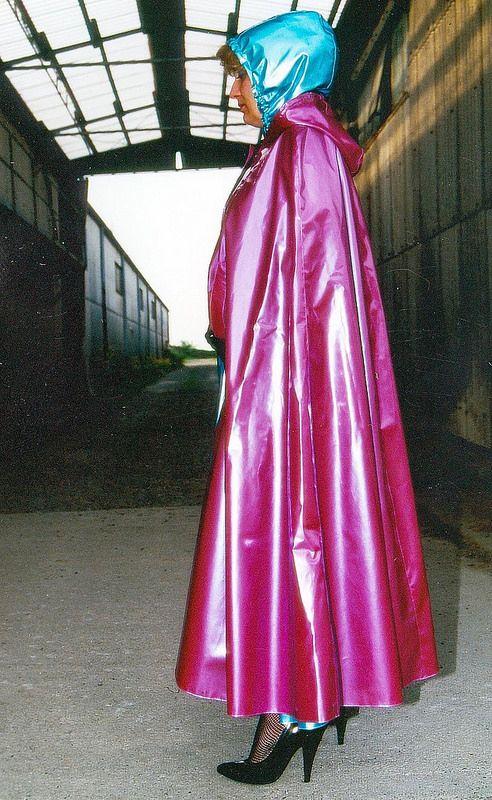Weinrotes Plagum Cape über türkisfarbenem Regencape mit aufgesetzter Kapuze