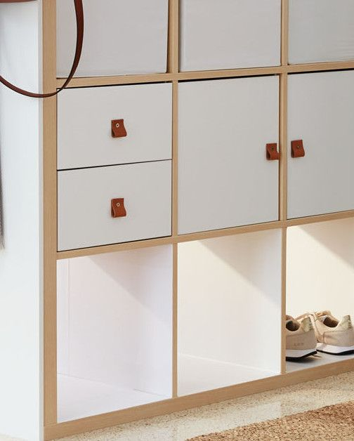 Dress up cabinet fronts and drawers with DIY pulls. Drill a hole in each panel, then attach a folded piece of leather with a small screw and nut.      IKEA Kallax shelving unit, in Birch Effect, $149; Kallax inserts with 2 drawers, in White, $20 each, and with door, in White, $15 each; and Dröna boxes, in White, $5 each, ikea.com.