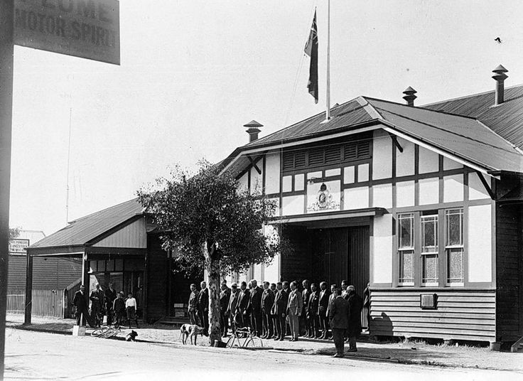 A ceremony in front of the Donald Soldiers' Memorial Hall, McCulloch Street. There is a flag at half mast and the men, who are all in civilian clothes, stand to attention, possibly for Armistice Day, xc1925. The hall burnt down in 1930.
