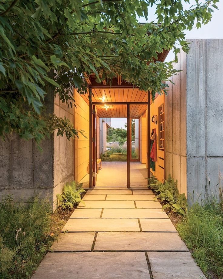 A palette of stone concrete and greenery greets guests at the homes front entrance.  #concrete #architecture #entrance  Photo by Chuck Choi Architecture by @peterroseandpartners by dwellmagazine