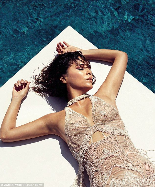 Catching some rays: Longoria laid out by the pool in her sheer white frock...