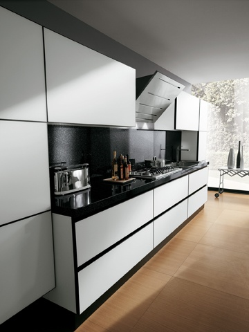 The doors of the Scenery composition  illustrated here are in mat White glass with  black aluminium frames. The use of undertop  grooves and access spacers for opening  the units further enhances their simple,  geometrical lines. Above the hob, another hood  option in stainless steel, with sophisticated,  modern design.