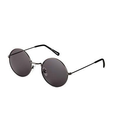 Negro. Gafas de sol redondas con montura de metal y plástico, y lentes teñidas. Protección UV.