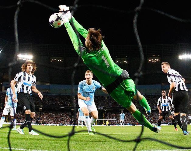 Tim Krul, guarda-redes do Newcastle, defende um cabeceamento de Edin Dzeko, do Manchester City, durante a partida da jornada inicial da nova temporada da Premier League (© © REUTERS / Darren Staples)