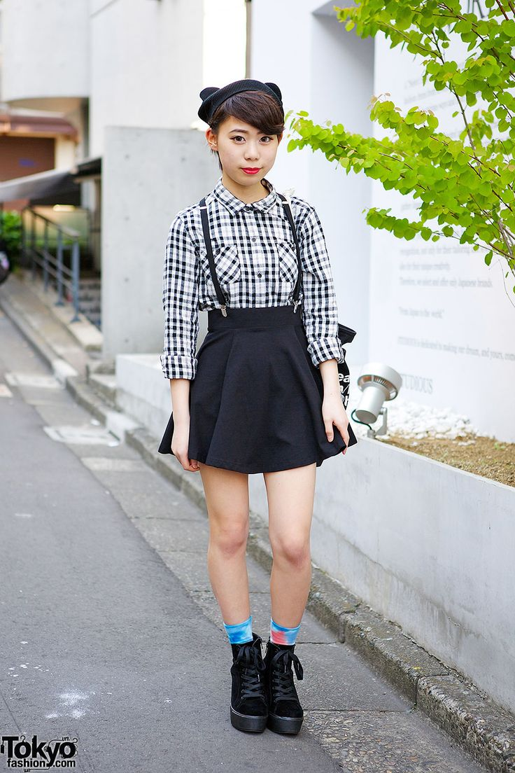 Harajuku girl in cat ears beanie, wearing a gingham shirt and suspenders skirt, tote bag and velvet ankle boots..