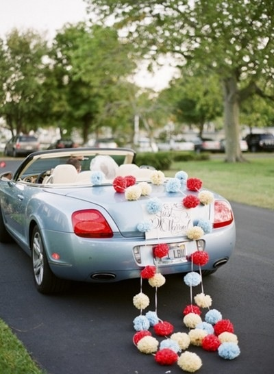 What a novel way to decorate the wedding car... with pom poms!!