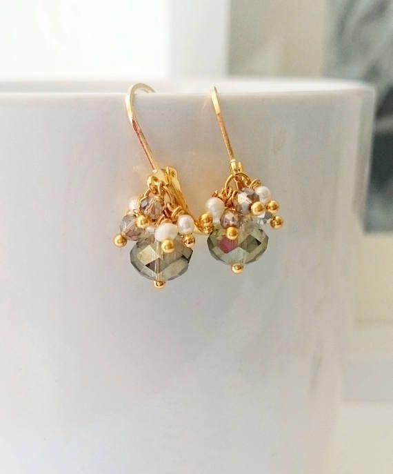 Zarte Ohrringe mit einem grauen großen Kristall in Kombination mit grauen kleinen Kristallen und naturellen Süßwasserperlen. Länge der Ohrringe ohne Klappbrisur: 1,2 cm Klappbrisur vergoldet mit 18 Karat Gold. Bleifrei, Nickelfrei und Cadmiumfrei.