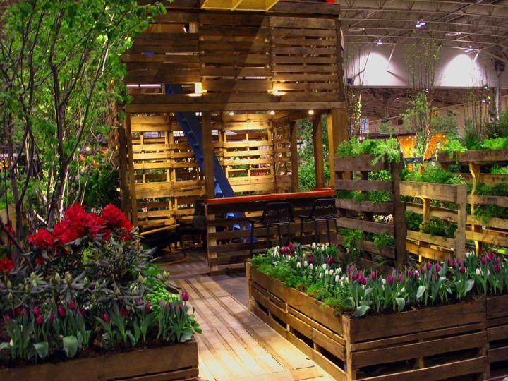 Reutilizar los pallets o tarimas de madera, para crear arriates para un jardín encantador. Sin contar que la terraza cubierta esta aprovechando el mismo tipop de material para lograr un espacio al aire libre congruente con su espíritu de ayuda al medio ambiente.