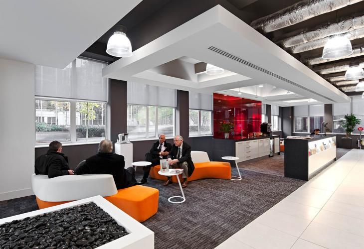 Well defined break out space / lounge. Ceiling and floor transitions. Use of color against stark background.