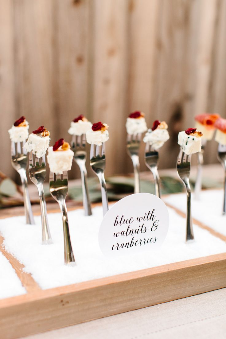 Another idea is to create a unique fork display using shallow wooden boxes. Cut cheese into small bite-size pieces, place on forks and add complimentary flavored items. Use craft foam to hold the upright forks in place and cover with coarse salt for a clean finish.