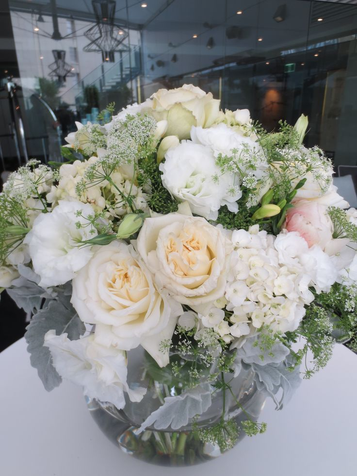 Vase arrangement of flowers in white and silver tones.