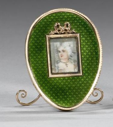 A Fabergé gold and enamel miniature photograph frame, workmaster Mikhail Perchin, St. Petersburg, late 19th century, the egg-shaped frame enamelled in translucent green over an engine-turned ground, the rectangular aperture with gold rim and ribbon surmount, open fretwork strut with suspension loop.