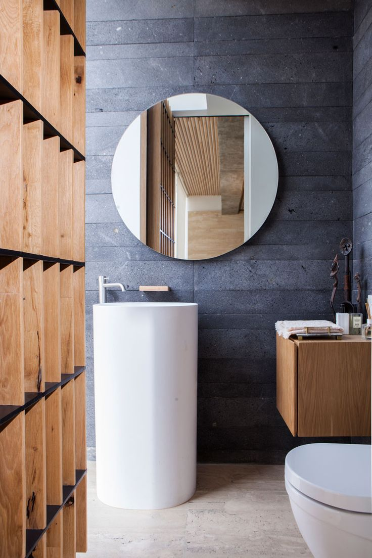 This modern bathroom features dark grey tiles and wood that have been paired with a simple standalone white basin and toilet.