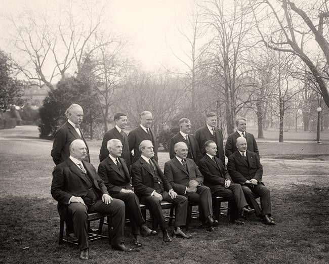 President Harding (seated, fourth from the left) & his Cabinet in 1921, including Vice-President Coolidge (to Harding's left) & Secretary of Commerce Hoover (behind Coolidge), plus Secretary of State Charles Evans Hughes, on Harding's right