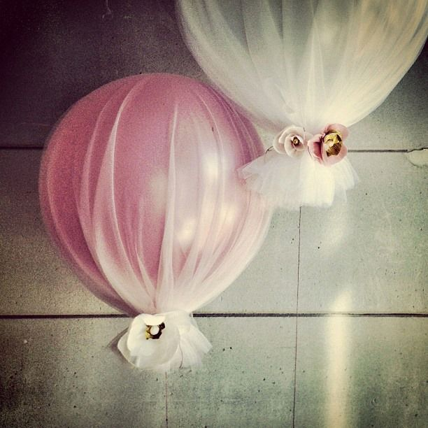 DIY Balloons covered in tulle and decorated with tiny synthetic flowers.