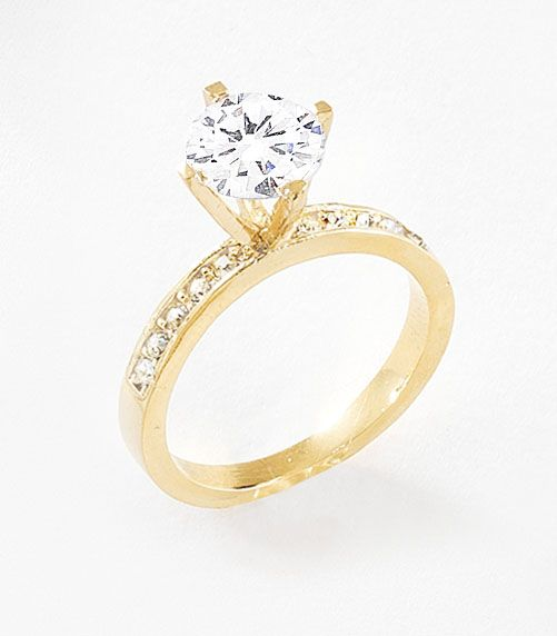 Anillo en 4 baños de oro de 18 kl con solitario de diamonice y pequeñas piedras de cristal en el frente del cuerpo del anillo.