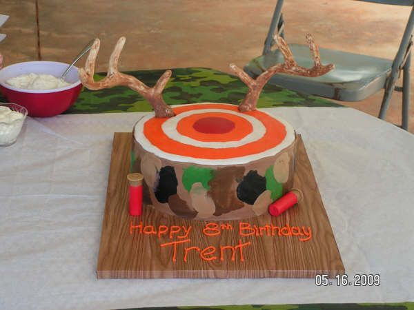 Target Antlers Camo Hunting cake - A mother contacts me about making a cake for her son's target practice/shooting range birthday party.  She says he has come up with a design for it - a target with a red bulls eye and deer antlers coming out of it.  I thought it was a cute idea and fit the theme of the party well.  The antlers are made from white and milk chocolate covering a wire and masking tape armature - thanks to Edibleart for the how to tips with the Mounted Deer cake photo.  The mom…