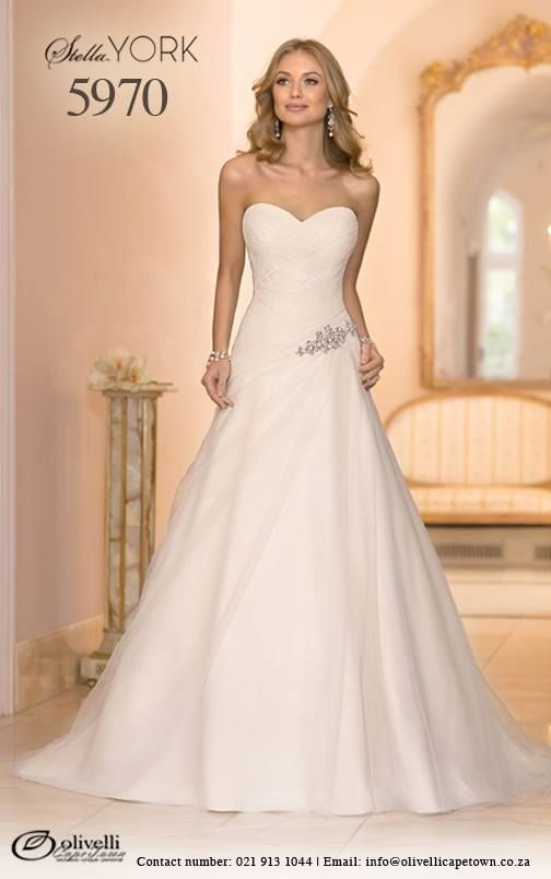 Another beautiful Stella York wedding gown! Style 5970, inspired by the hottest red carpet trends, is a Tulle A-Line dress with amazing detail. The asymmetrical ruched bodice, the sweetheart neckline and the high back with the chapel train will make your big day a dream come true! #StellaYork #OlivelliCT #Wedding #Gown #Dress