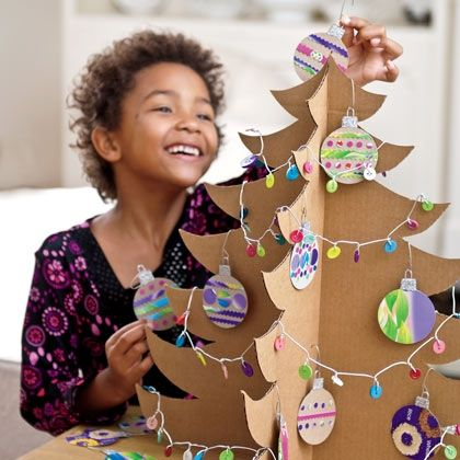 Cardboard tree with paper garland and baubles. Folds away easily when not displayed 11 months of the year.     To make the tree - cut two identical tree shapes from an old cardboard box. Cut a vertical slit from the centre of Tree1 to the top, and the centre of Tree2 to the bottom. Slide Tree 2 onto Tree 1. Decorate with home-made paper decorations.