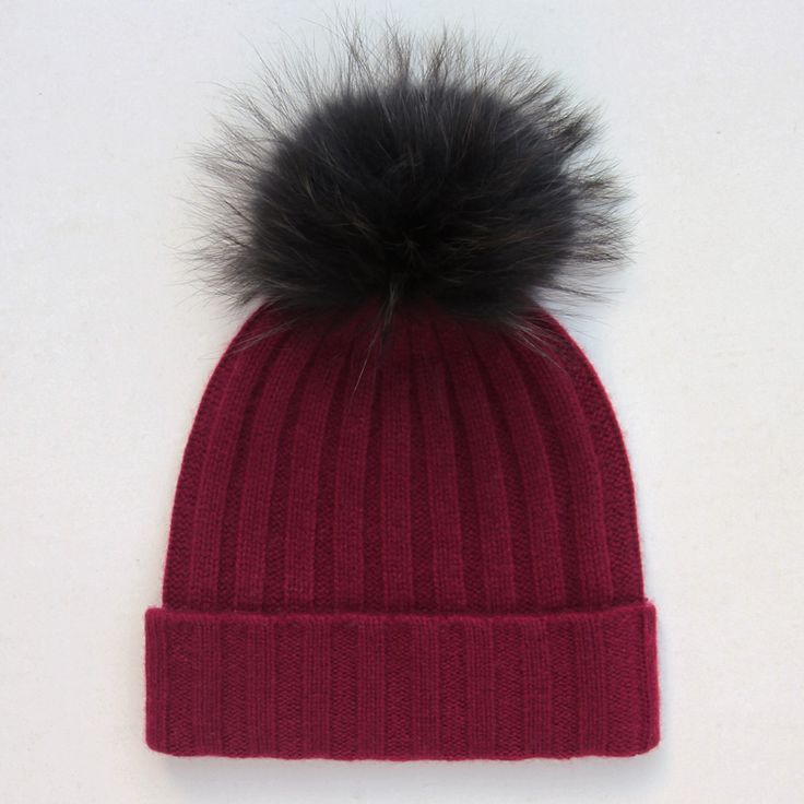 Luxurious and warm this fluffy pom pom cashmere bobble hat is perfect for the autumn and winter months. Knitted from 100% cosy cashmere in burgundy and topped with an irresistibly fluffy pom pom in black. The fur bobble is attached by a button and can be removed for washing. Why not change up your look with any of our separate fur pom pom attachments.