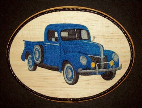 This unique 1940s Ford Truck Embroidery Balsa Wood Art, Classic Car Decor combines the warmth of wood with the raised texture of 12 different thread colors and 50,861 stitches. The design was machine embroidered into a sheet of balsa wood, then cut and mounted on an oak stained 7 x 9 x 1 plaque. The black leather braided trim was added before a clear protective, non-yellowing acrylic matte finish was applied. A brass hanger is attached to the backside making it ready for hanging.    Balsa…