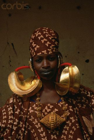 Malian Woman in Traditional Dress - A Peul woman wears large gold earrings. She also has her lips tattooed in the traditional style. Mali, northwestern Africa.