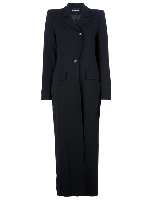 Black wool blend coat from Ann Demeulemeester featuring structured shoulders, a notched lapel, a an off centre top button fastening, a central button fastening, a fitted waist, two flap pockets, and long sleeves.