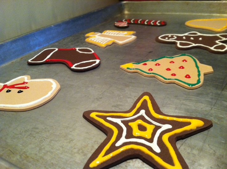 Foam sheets cut in cookie-cutter shapes, decorated with puffy paint. Play baking-Christmas-cookies!