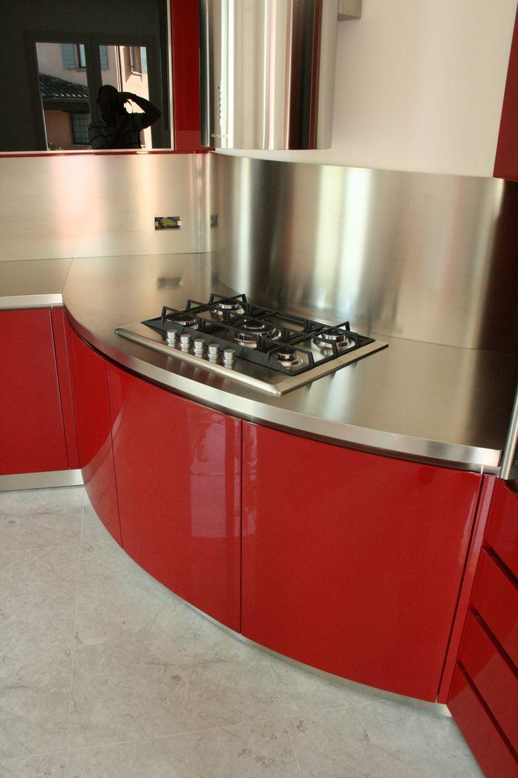 Cucina moderna senza maniglia con ante laccate rosso lucido. Il piano di lavoro è realizzato in acciaio satinato, le ante dei pensili sono in vetro Lacobel nero con cornice in acciaio inox satinato.