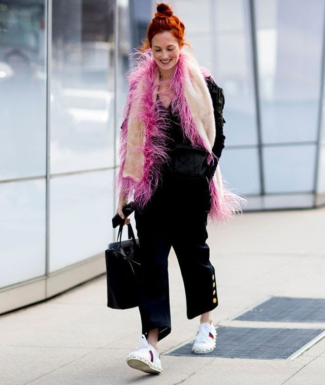 Taylor Tomasi Hill wears a feather scarf at fashion week