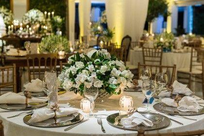 mesa de casamento com sousplat de prata e flores brancas com velas madame fiori