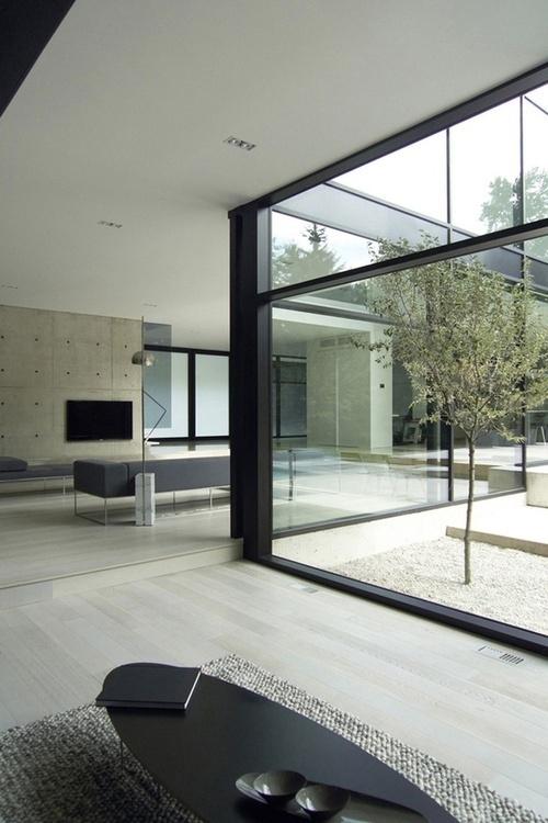 Fine detaljer: Sorte vinduer, lyst trægulv, hvid/sort loft og beton væg. Flot og grafisk