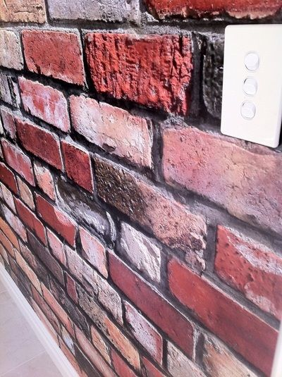 Incredibly realistic digital print on wallpaper of red face brick. By jmb paperhangers.