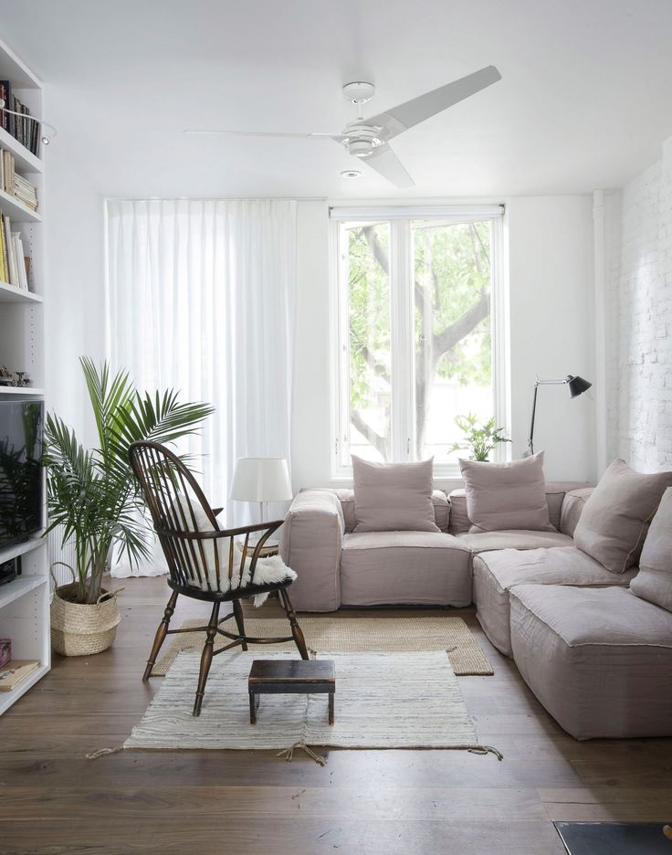n the living room a beige sectional sofa is followed by a statement industrial floor lamp, a white rug and greenery. A rustic open back chair is placed in front of a white wooden bookcase. Large windows allow plenty of natural lighting into the space.
