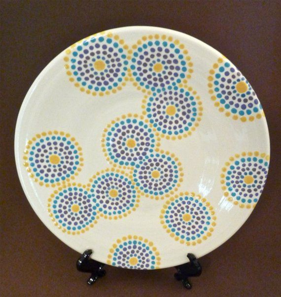 This lovely earthenware plate is wheel thrown. Each of the individual dots was hand painted, and some of the dotted circles creep over the side