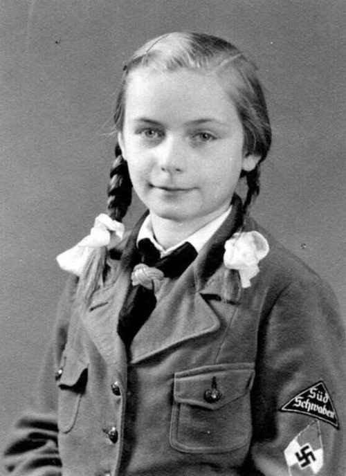 The girl is wearing a Bund Deutscher Madel uniform. BDM being the female unit of the Hitler Youth
