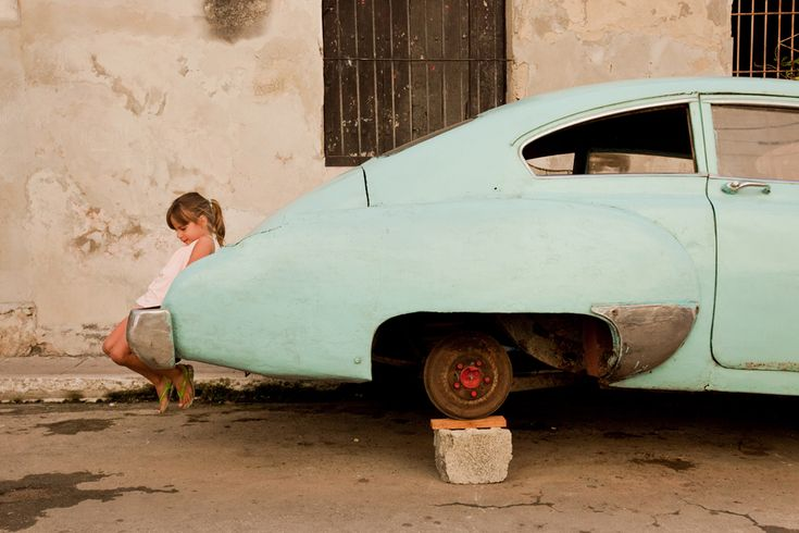 The classic American car has become a symbol and staple throughout Cuba. In the back streets of Havana, one who has yet to learn of the country's history, shows her innocence at play.