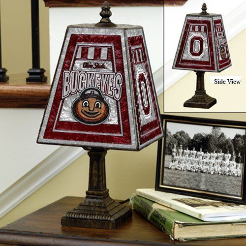 Ohio State Buckeyes Memory Company Art Glass Table Lamp NCAA College Athletics Fan Shop Sports Team Merchandise by Memory Company. $69.95. Your passion for play on the field be seen in your home decor. The Memory Company®  team art glass table lamp is designed with the team logos on 2 sides and decorated in team colors. The 14.5-in x 7.375-in glass table lamp sits on a brass-based resin stand.