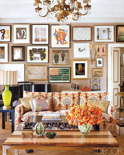 A statement gallery wall | Lindsey and Kristen Buckingham's Los Angeles home | An art collection grows over time to include pieces of different styles and varying subjects—each inspiring on its own, but stunning when displayed in a group. Many of the Buckingham's favorite pieces create a bold, energy-filled gallery wall that brings color to the room. Designer Kristen Buckingham used the entire wall space and was sure to stager the works by color, size and frame type.