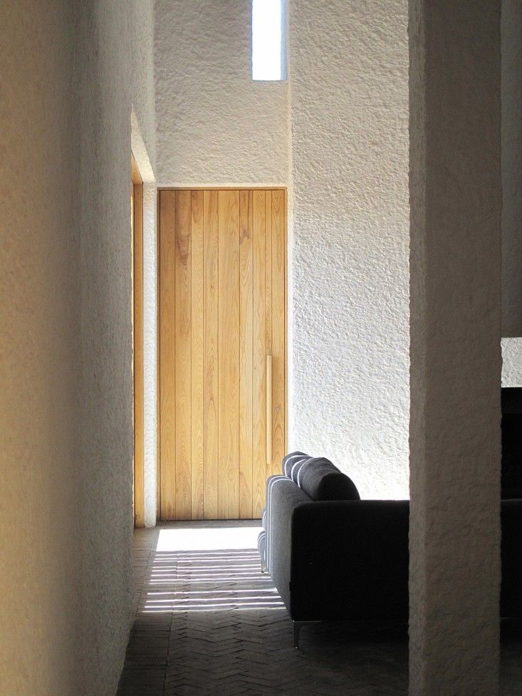 Limed-washed plaster walls, ash wood doors and dark brick floors in living room of Swartberg House by Openstudio Architect in Great Karoo, South Africa | Remodelista