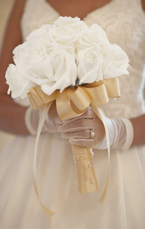 Flawless white roses, wrapped in golden satin and miniature pearls, the ideal wedding bouquet to compliment a vintage pearl engagement ring