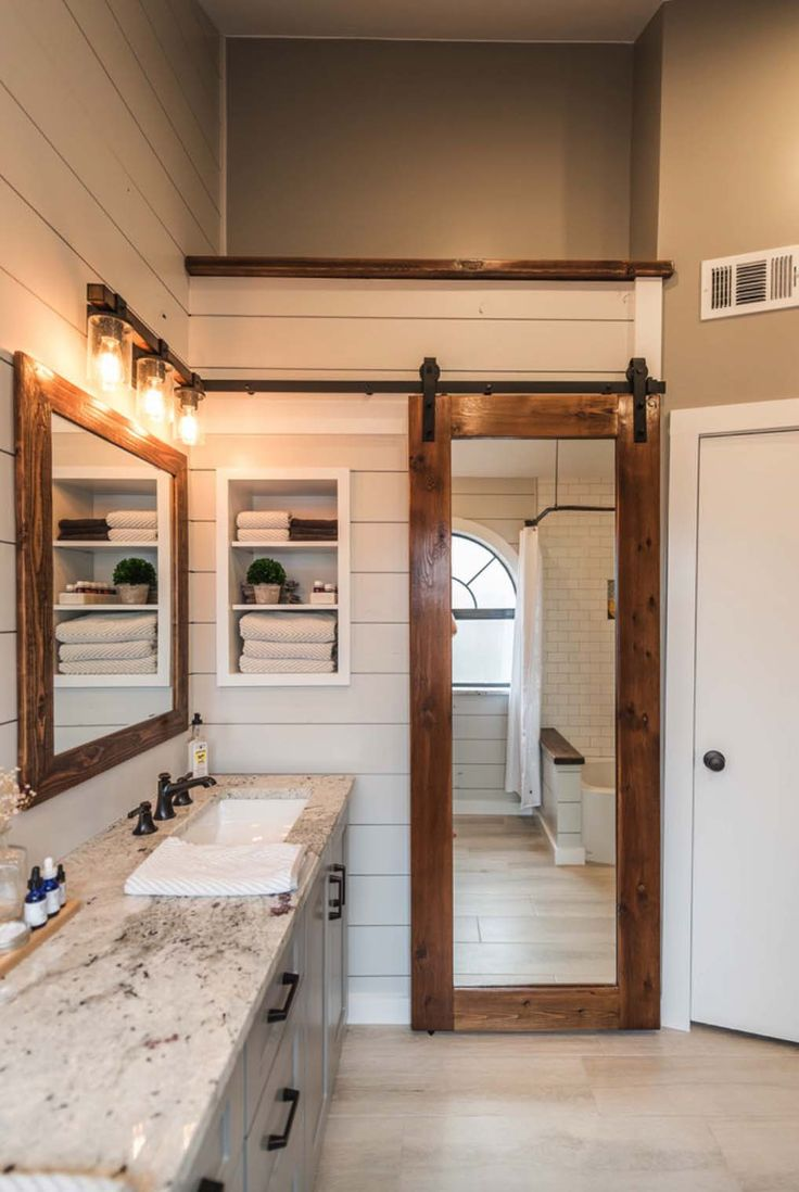 The mirrored barn door was custom-made for this modern farmhouse project. The countertops are Colonial White Granite. The shiplap is painted in Sherwin Williams Crushed Ice, while the vanity is painted in Sherwin Williams Pavestone. The walls are Sherwin Williams Pussywillow and the trim is Sherwin Williams Extra White. (via Irwin Construction)