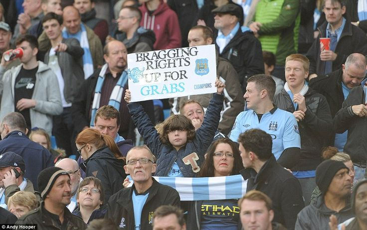 A young Manchester City fan holds up a homemade poster declaring that there are 'bragging rights up for grabs' in the Manchester derby