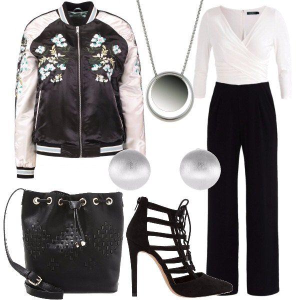 Una jumpsuit bianca e nera in jersey è accompagnata dal bomber bianco e nero con stampa floreale. Abbiniamo una collana in acciaio, un paio di orecchini a lobo, un paio di scarpe molto particolari, con tacchi a spillo e una borsa a secchiello nera.