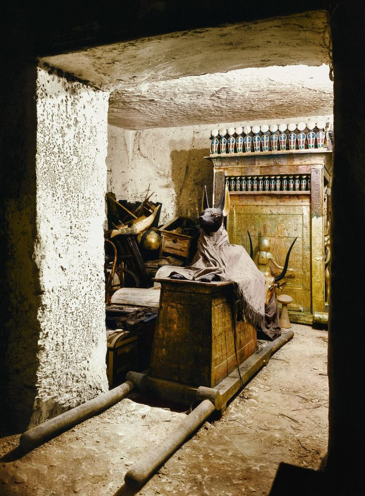 """c. 1923: A statue of Anubis on a shrine with pallbearers' poles in the treasury of the tomb. Image: Harry Burton (c) The Griffith Institute, Oxford. Colorized by Dynamichrome for the exhibition """"The Discovery of King Tut"""" in New York."""