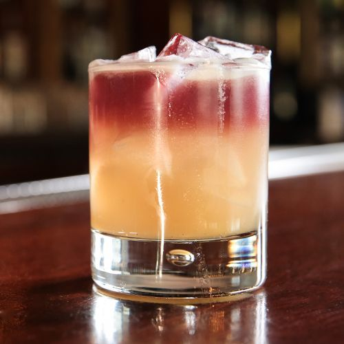 New York Sour:  2oz Rye whiskey or bourbon, ¾oz Simple syrup (one part sugar, one part water), 1oz Fresh lemon juice, 1 Egg white (optional), ½oz Red wine.  Add all the ingredients except the wine to a shaker and fill with ice. Shake well and strain into a rocks glass filled with fresh ice. Carefully pour the wine over the back of a spoon so it floats on top of the drink.