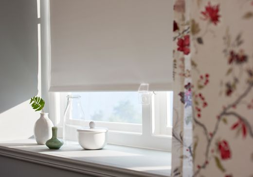 A close-up image of a lowered block-out blind, a floral curtain and some small vases in a window.