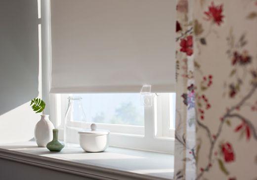 Nahaufnahme eines Verdunklungsrollos und INGMARIE Gardine mit buntem Blütenmuster, vor dem Fenster ein paar kleine Vasen.