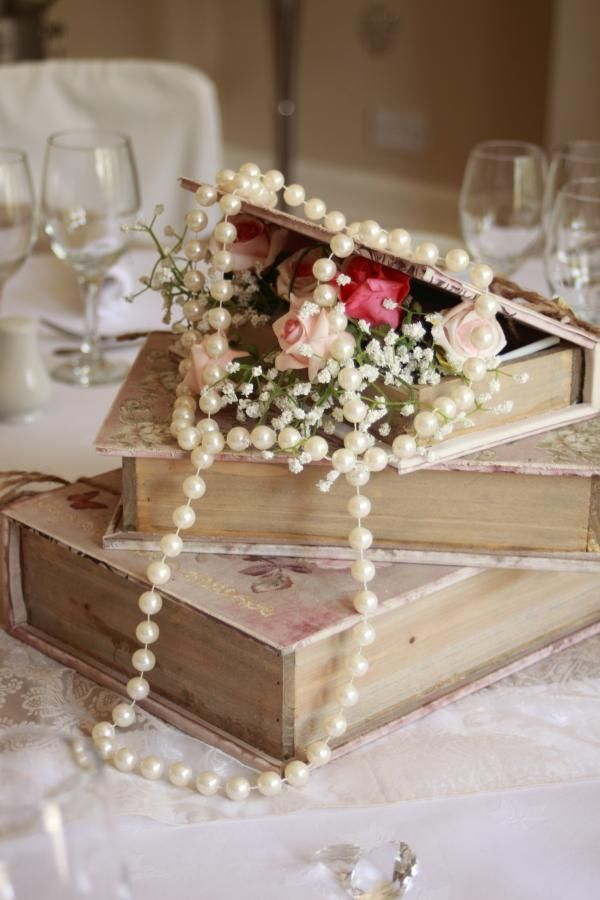 centerpieces with books and pearls | Vintage books with roses and pearl draping